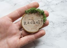 Rustic wood slice and moss wedding place settings / escort cards, perfect for an outdoor woodland or barn wedding. A lovely personalised wooden favour for a rustic theme, these place cards make great keepsakes for your guests to remember your special day. ▼▼▼▼▼▼▼▼▼▼▼▼▼▼▼▼▼▼▼▼▼▼▼▼▼▼▼▼▼▼▼▼▼▼▼▼   ♡ PRODUCT OVERVIEW ♡  - The names are stamped by hand on to a small birch wood slice with black ink.  - Vibrant green decorative reindeer moss is then added to the wood slices. The moss is dried an...