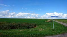 Kruising Konkelswei/Hoarnestreek in Oosterbierum. Blik op de zeedijk met een prachtig wolkendek.