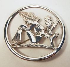 Vintage sterling silver brooch signed Truart •Round repousse style, with Mexican wearing sombrero next to cactus •Very detailed •Signed Truart