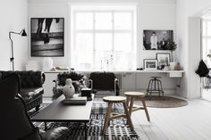 white, grey living room .. Love this shelf under window, chesterfield sofa, rugs over director's chairs are funky... bit 'cold' and stark black and white, make a little warmer