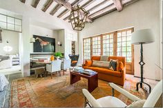 Next to the kitchen is the family room, done in orange and yellow. Under the horse painting is a banquette upholstered in stripes.  Out the French doors is the pergola and dining table outside.  Beautiful antique rafters on the ceiling.