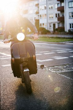 Man driving old school scooter by Urs Siedentop #stocksy #realstock
