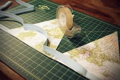 DIY: Map Bunting perfect for a wedding or bridal shower or travel themed party! I love crafts! Update: I made this using an old atlas and maps for my daughters travel themed wedding shower and it was a hit!! I hole punched top corners and ran twine through to hang. It looked awesome!