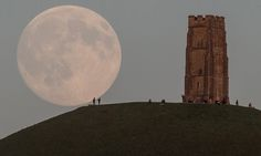 The moon rises over people gathered on Glastonbury Tor, Somerset, England on July 30, 2015. Tonight it will happen again and be called a Blue Moon. The last time this happened was in 2012 and there isn't due another until 2018.