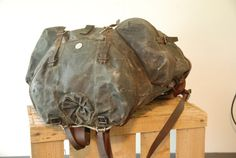 Swiss Military or Army backpack or rucksack from 1946, made from canvas and leather. The bottom of the bag is reinforced with very strong tan saddle leather. The same leather is used for the shoulder straps (which are attached to the bottom of the bag) and the straps on the front of the bag that close the large front pocket and the backpack itself, as well as some additional straps that can be used to hold items on the outside of the bag.  The backpack is heavy and very, very sturdy…
