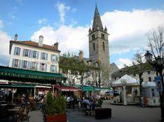 Barcelonnette: Place Manuel : tour Cardinalis (tour de l'Horloge), maisons, terrasses de cafés et manège - France-Voyage.com