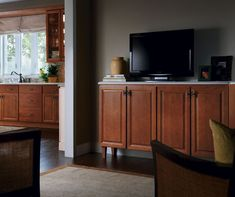 This living room cabinet matches the cabinets in the adjoining kitchen, defining the space you're in while helping to maintain a cohesive look. Living Room Cabinets, Living Room Storage, Homecrest Cabinets, Sectional Furniture, Melbourne House, Contemporary Bar, Transitional Kitchen, Cabinet Styles, Other Rooms