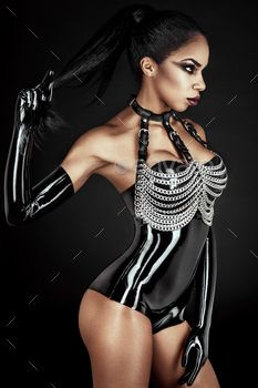Portrait of sexy woman in black latex outfit with metal chains