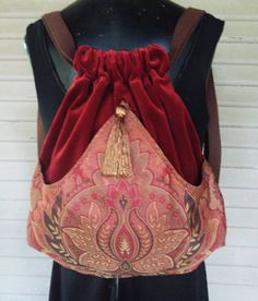 Original handmade backpack made with a brick red cotton velvet. The outside pocket of a jacquard tapestry in rose, brown and brick red arches in
