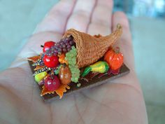 Dollhouse miniature cornucopia with gourds, pumpkins, apples, pears, 3 kinds of grapes, and leaves. Handmade by wendyoriginals.