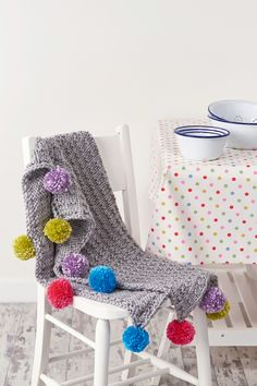Knitted baby blanket pattern with pom pom trim