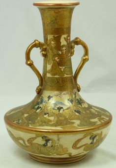JAPANESE GOLD SATSUMA PORCELAIN HANDLED VASE  Antique Japanese hand painted Satsuma porcelain handled bottle form vase. Has hand painted design depicting wise men and maidens in seated positions. Embellished throughout with gilded designs and beading. Holds Gold Satsuma marks to bottom. 19th century.