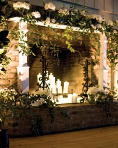 A brick fireplace draped with roses, hellebores, and magnolia leaves provides a romantic backdrop for wedding vows