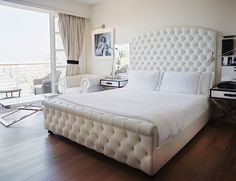 Hollywood Regency style bedroom with tall white curved bed frame
