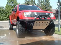 Lifted Nissan Frontier with custom offroad front bumper ad skid plate.
