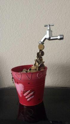 Ein Eimer voll Geld mit schwebendem Wasserhahn