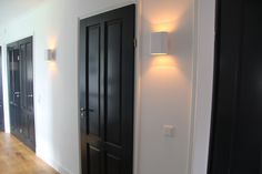 Zwarte deuren in de gang met witte kozijnen en prachtige Duell lamp; wall white met champagne kleur van binnen.