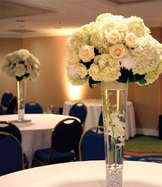 Contemporary & elegant centerpiece design: tall trumpet vase, white hydrangeas, vendela roses, feathers, white dendrobium orchids & glass crystals immersed in water.