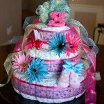 Diaper Cake with tutorial.  This is the most straightforward instruction I have seen.  Use more baby toys, bath items etc, to replace some of the flowers if you wish...