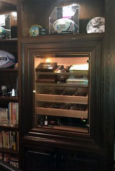 Custom built-in humidor with glass picture frame window to fit into existing shelving.