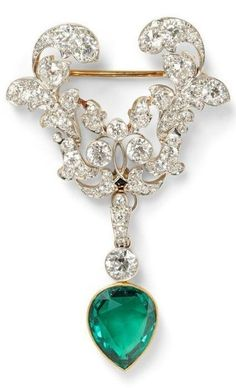 Edwardian Emerald and Diamond Brooch, the drop set with a pear-shape emerald, surmounted by a bezel-set old European-cut diamond and suspended from a scrolling foliate brooch set with old European-cut diamonds, platinum-topped gold mount. #Edwardian #brooch by chrystal