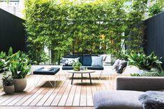 Une pièce à vivre extérieure qui joue la carte du noir et blanc réchauffée de bois