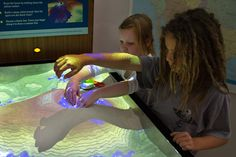 """Children at the University of California, Davis', Tahoe Environmental Research Center run their hands through the sand in the """"Shaping Watersheds Interactive Sandbox,"""" an augmented reality sandbox in which users can form mountains, lakes and rivers while a 3-D camera and digital projector allow them to create virtual topography in real time, even making it """"rain."""" Photograph by Jim Markle"""