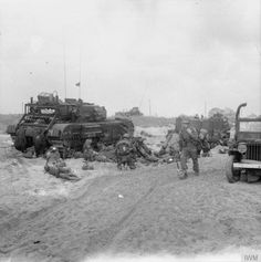 Troops of 3rd Division on Queen beach, SWORD area. On the left, medics attend to wounded next to a disabled Churchill AVRE from 5th Assault Regiment, Royal Engineers. The AVRE is a SBG bridge carrier, and has already laid its bridge