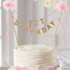 Birthday cake topper reads '1st Birthday' in glitter felt strung between two pom-pom topped wooden dowel posts.