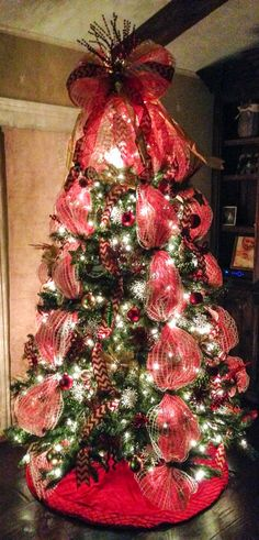 Deco mesh Christmas tree with red chevron burlap ribbon and mesh bow tree topper. Red deco mesh is layered under white window pane mesh for extra depth and color.