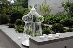 This powdercoated white bird cage (sans bird!) makes a great focal point without being too heavy.   Works very well with white garden furniture (see EMU round chairs and Schultz table).