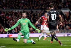 Liverpool's Brazilian midfielder Philippe Coutinho (R) shoots past Manchester United's Spanish goalkeeper David de Gea (L) to score their first goal during the UEFA Europa League round of 16, second leg football match between Manchester United and Liverpool at Old Trafford in Manchester, north west England on March 17, 2016. / AFP / OLI SCARFF