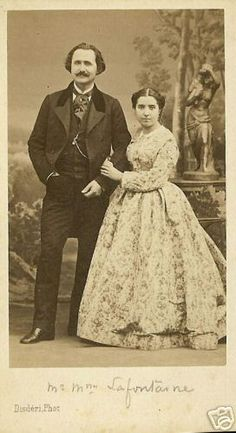 Finely dressed couple. Gent in frock coat, vest with watch chain, trousers, shirt and cravat. Lady in floral print with high body, demi open sleeves, pleated skirt.