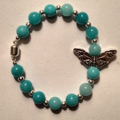 Spring 2013 Collection to be released mid-January.  7 1/2 inch bracelet made with teal stone beads with a large butterfly spacer bead and a magnetic clasp. $19.99