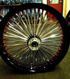 "Ridewright 23"" custom wheel, with black soft-lip rim, jewel-cut, stainless steel spokes, with mirror finish, and red nipples."