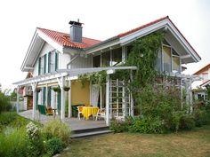 Dieses wunderschöne Holzhaus vereint gekonnt und stilsicher das klassische Wohnhaus mit einem modernem verglasten Wintergarten.