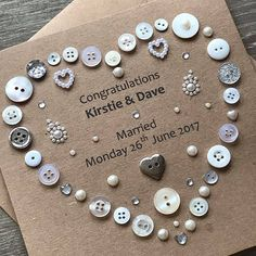 This button art designed Wedding card is a perfect greetings card for newlyweds. What a beautiful piece of handmade art to mark their special day, which can also be framed afterwards. With white, cream and silver buttons and pearl embelishments and gems to make this card look