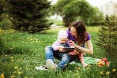 a mom reading to her baby in a park