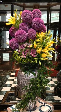 Purple Pom Chrysanthemums and yellow iris-type flowers. Stunning arrangement and table design.