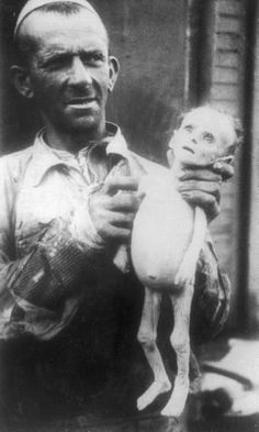 Man holds aloft the corpse of a starved infant in the Warsaw Ghetto, May 1941