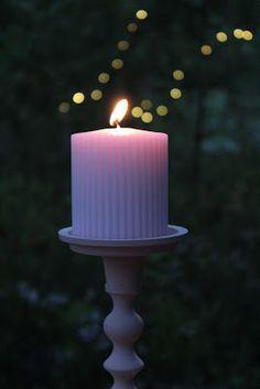 Puutarhajuhlissa ompi tunnelmaa. Vaaleanpunainen kynttiläjalka juhlistuu vaaleanpunaisella vekkikynttilällä