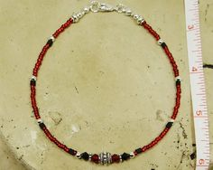 Minimalist anklet ankle bracelet made with a decorative silver pewter bead in the center, deep red crystal donuts, jet black Swarovski crystals, and red Czech glass seed beads with jet black hex seed accents. All metal beads are lead/cadmium-free Tibetan silver; clasp and other finishing-off pieces are silver-plated. SO pretty for those who love red and black together. Very wearable. Lightweight. Minimalist jewelry. Beaded anklet. Red anklet. Minimalist anklet. Spring. Summer. Beach. Va...