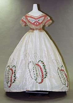 Evening Dress, circa 1864: Ivory silk taffeta set of bodice and skirt; worn over crinoline; chenille fringe on bodice, waist and back of skirt; embroidery of loops of flowers and leaves and black rectangles. Via KCI.