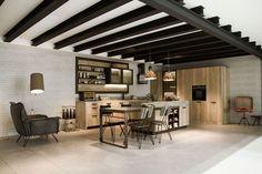 îlot de cuisine en bois et béton, suspensions en laiton, poutres apparentes au plafond et lampadaire design