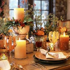 With one pillar candle elevated, others remain on the tabletop near glass votive holders, creating a glow of light for any autumn dinner. Airy stems fill twin pots embellished with tangerines, add a few fall leaves and nuts for color.