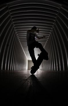 This image demonstrates a frame within a frame, the tunnel that Rodney Mullen is performing his trick in, is acting as a frame in the background. Leading lines are also present.