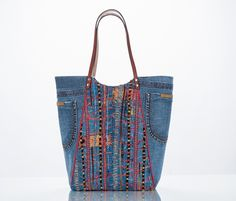 This Eco Fashion bag is one-of-a-kind; built to carry a large and heavy load. Materials:  Upcycled blue jeans (the pockets still work!) and embroidered Chicos jacket.  Measures:  15.5high.  18w at the top with a 5w bottom  Handcrafted leather strap handle 11.5 drop  Inside:  Yellow lining  One zip pocket, one slit pocket - both wide and deep  Metal feet on leather protect the bottom and help it stand tall  Magnetic snap closure.  As will all the goodies from the studio; this bag was…