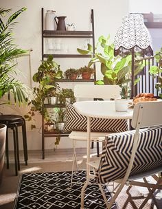 A balcony decorated with a small table, floor lamp, two rugs, a shelf, plants and extra stools.