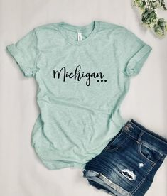 """Super cute and soft """"Michigan"""" women's graphic tee! This soft t-shirt has a looser fit, for comfort and functionality. Beautiful Heathered Mint color with solid black graphic. ►SHIRT SPECS: -52% combed and ringspun cotton, 48% polyester -4.2 oz. -Unisex fit -Pre-shrunk -Soft, heathered fabric Custom Tickets, Mint Color, Love T Shirt, Graphic Tee Shirts, Cute Shirts, Solid Black, Trending Outfits, Michigan, Clothes"""
