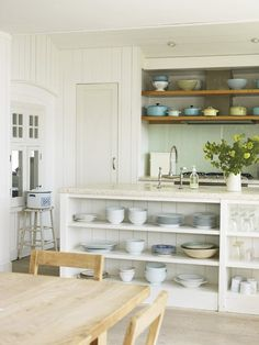 Casual Open Shelves    Display pretty pots and dishes for a bit of colour    Rows of open shelves make this light and airy kitchen space feel relaxed and informal. The freestanding island unit that houses the sink keeps the cook connected to the dining area while offering storage space and cleverly concealing potentially messy work areas.        * Source: Pale & Interesting (2011 Ryland Peters & Small), by Atlanta Bartlett & Dave Coote      * Photographer:          Polly Wreford